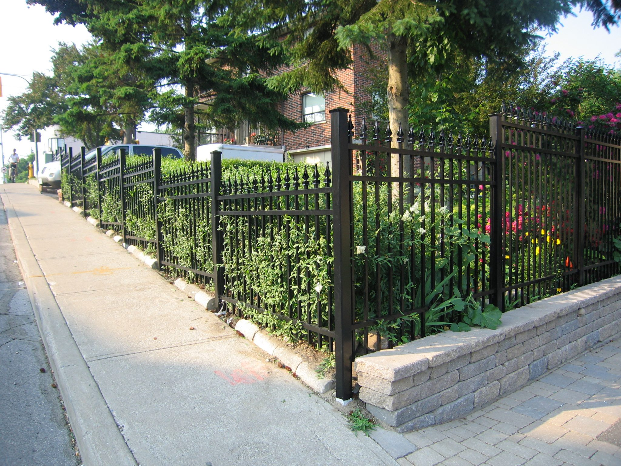 Stone bricks under black picket fence